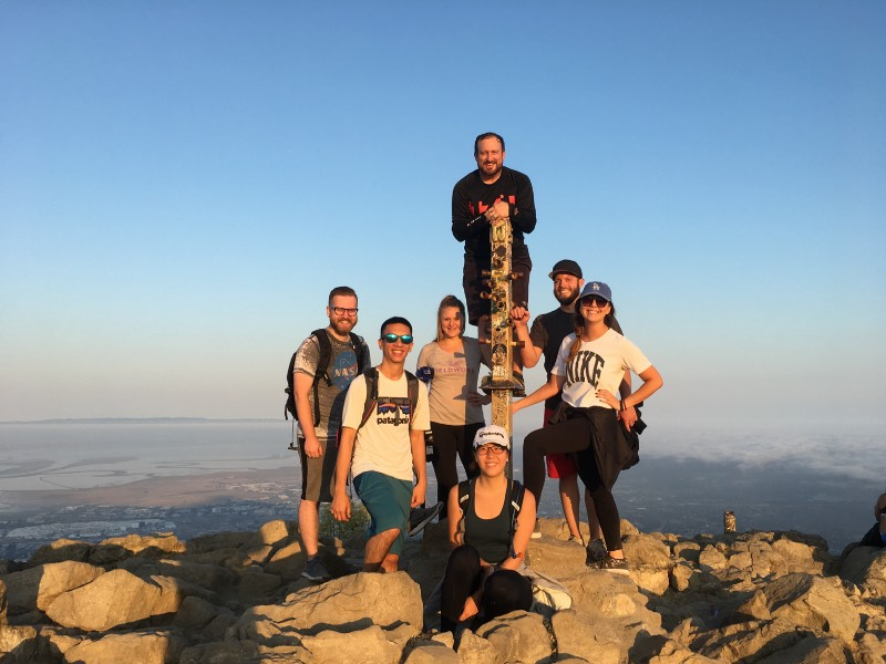 A group of Zooka Team members hiking and posing at the top of the hill.